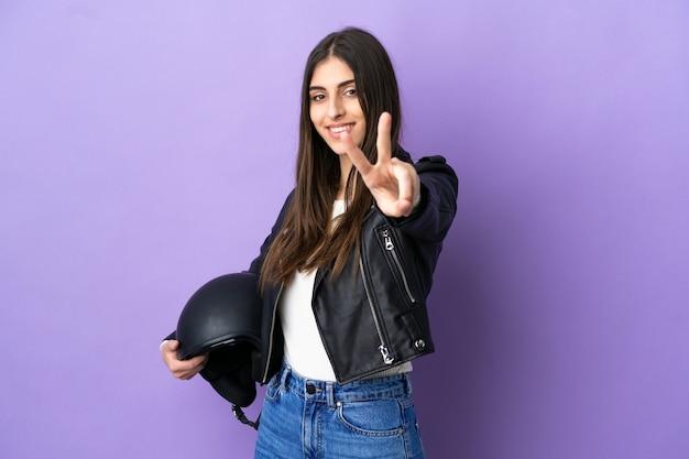 Молодая кавказская женщина с мотоциклетным шлемом изолирована на фиолетовом фоне, улыбаясь и показывая знак победы