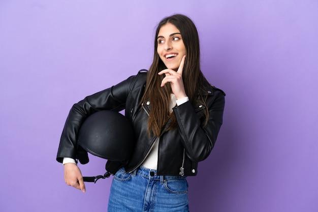 보라색 배경에 오토바이 헬멧을 쓴 백인 젊은 여성이 올려다보는 동안 아이디어를 생각하고 있다
