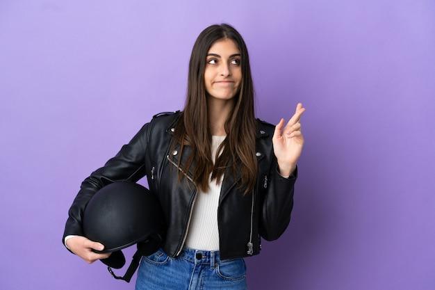 Молодая кавказская женщина в мотоциклетном шлеме изолирована на фиолетовом фоне со скрещенными пальцами и желает лучшего