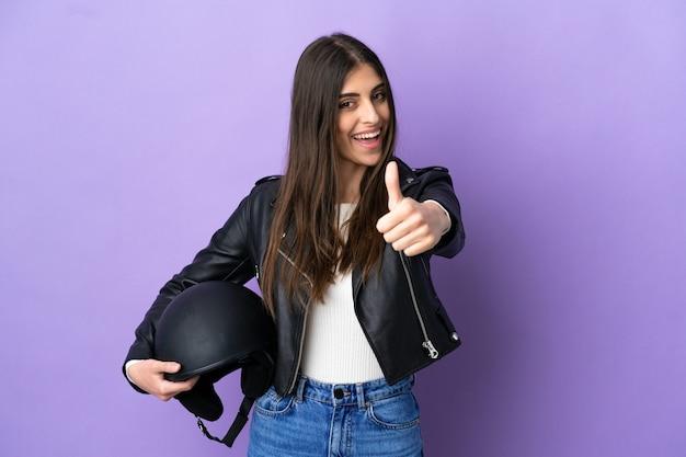 Молодая кавказская женщина с мотоциклетным шлемом изолирована на фиолетовом фоне с большими пальцами руки вверх, потому что произошло что-то хорошее