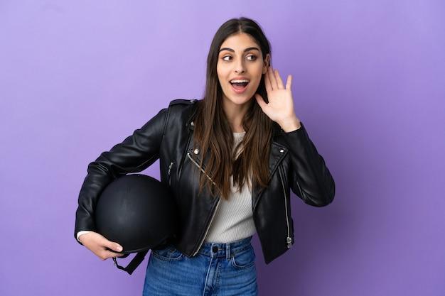 Молодая кавказская женщина с мотоциклетным шлемом на фиолетовом фоне