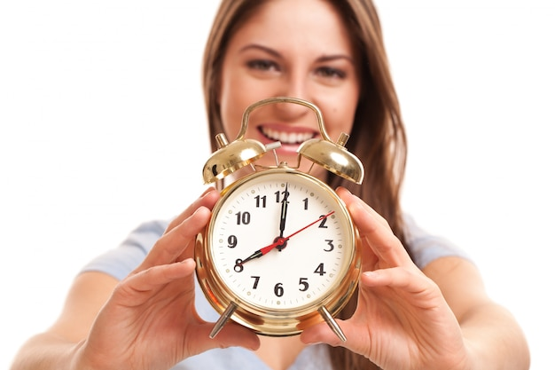Young caucasian woman with alarm clock