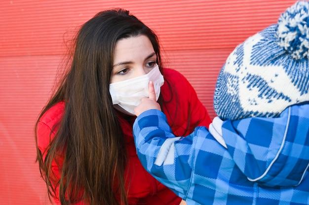 Молодая кавказская женщина с аллергией нося защитную маску. маленький мальчик и его больная мама на улице.