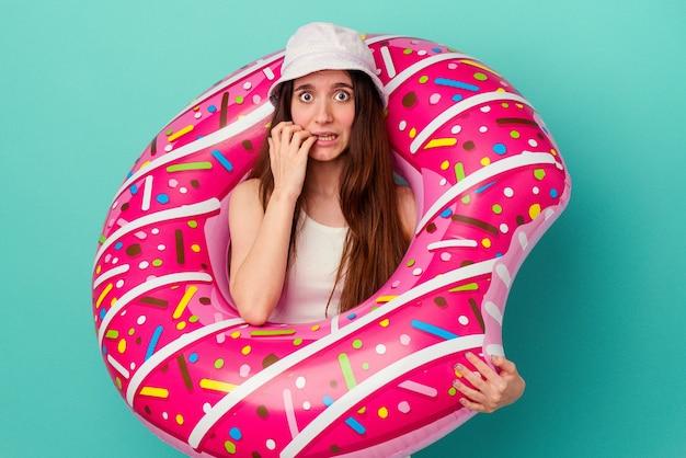 파란 배경에 풍선 도넛을 들고 손톱을 물어뜯고 긴장하고 매우 불안한 젊은 백인 여성.