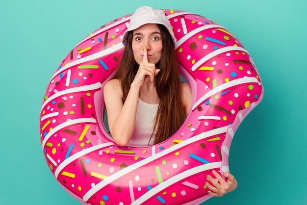 Молодая кавказская женщина с надувным пончиком, изолированным на синем фоне, хранит секрет или просит молчания.