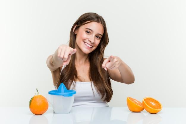前を指しているオレンジジューサー陽気な笑顔で若い白人女性。
