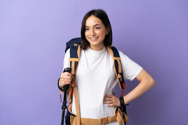 バックパックとトレッキングポールを持つ若い白人女性は、腰に腕と笑顔でポーズを青で分離