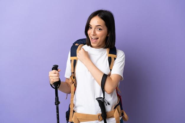 Молодая кавказская женщина с рюкзаком и треккинговыми палками изолирована на синей стене празднует победу
