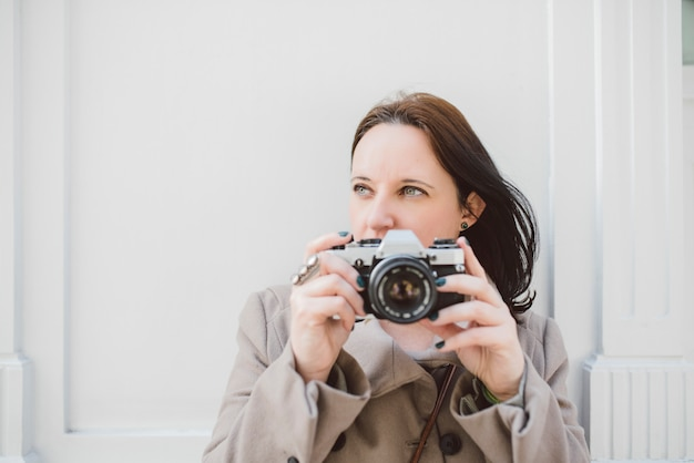 Young caucasian woman with blue eyes in a brown coat waiting on a white wall with her old camera.