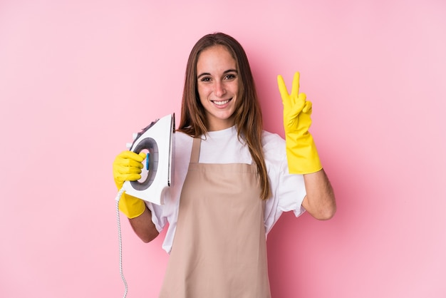 指で2番目を示している孤立した服の鉄を持つ若い白人女性。