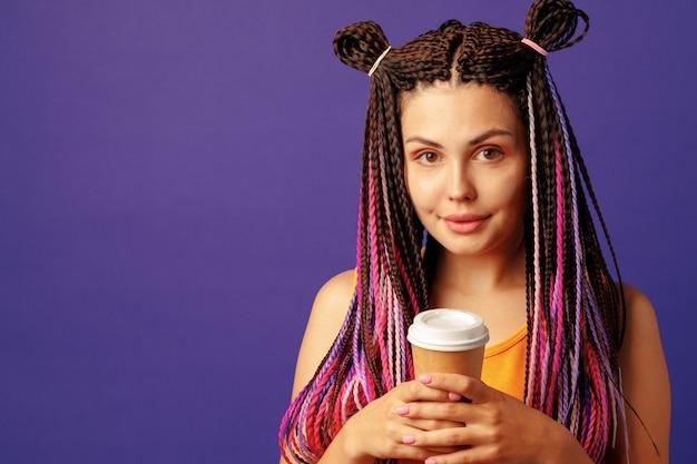 보라색에 커피 한 잔을 들고 화려한 긴 cornrows와 젊은 백인 여자