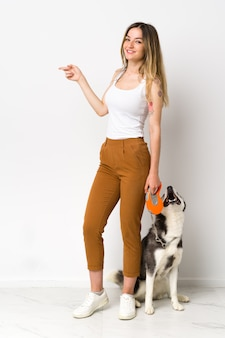 Young caucasian woman with dog over isolated wall