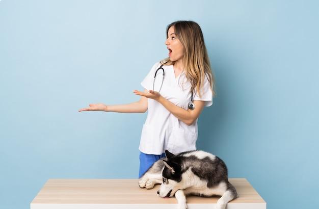 孤立した壁の上の犬を持つ若い白人女性