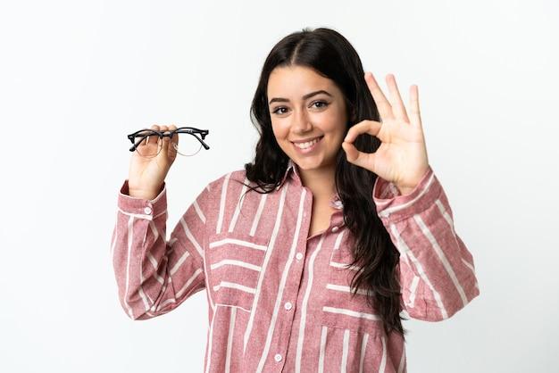指でokサインを示す白で隔離の眼鏡と若い白人女性