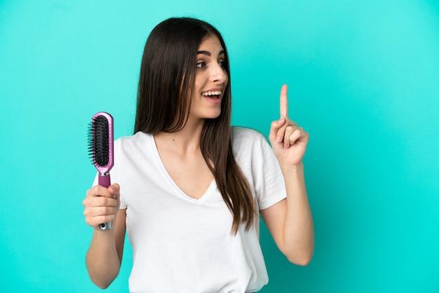 指を持ち上げながら解決策を実現することを意図して青い背景で隔離の髪の櫛を持つ若い白人女性