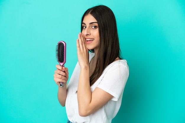 何かをささやく青い背景で隔離の髪の櫛を持つ若い白人女性