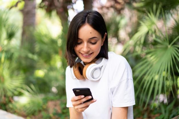 Молодая кавказская женщина с наушниками на открытом воздухе, отправляя сообщение с мобильного телефона