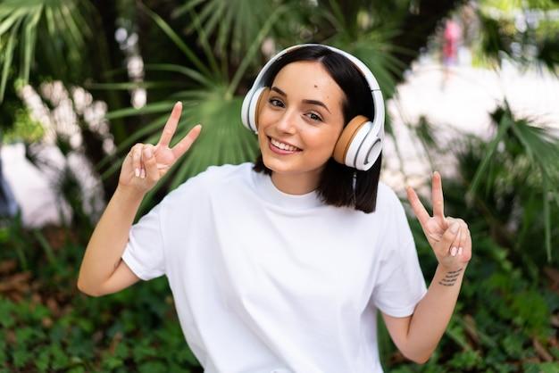 両手で勝利のサインを示す屋外でヘッドフォンを持つ若い白人女性