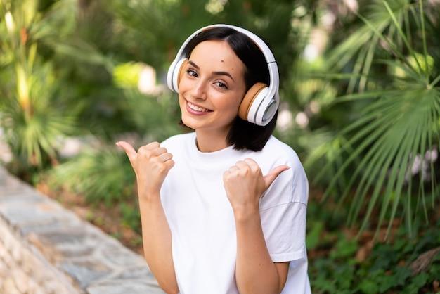 Молодая кавказская женщина с наушниками на открытом воздухе с большими пальцами руки вверх жестом и улыбкой