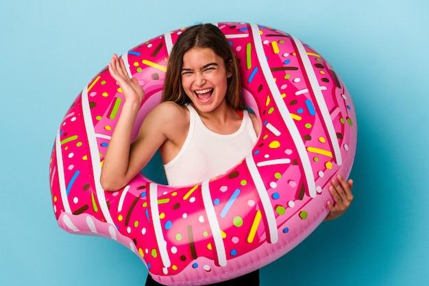 즐거운 놀라움을 받고, 흥분하고 손을 올리는 파란색 배경에 고립 된 풍선 도넛과 젊은 백인 여자.