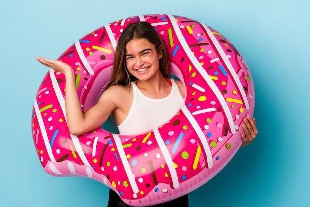 손바닥에 복사 공간을 표시 하 고 허리에 다른 손을 잡고 파란색 배경에 고립 된 풍선 도넛과 젊은 백인 여자.
