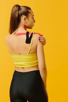 彼女の腹と脚、黄色のキネシオロジーテープを持つ若い白人女性