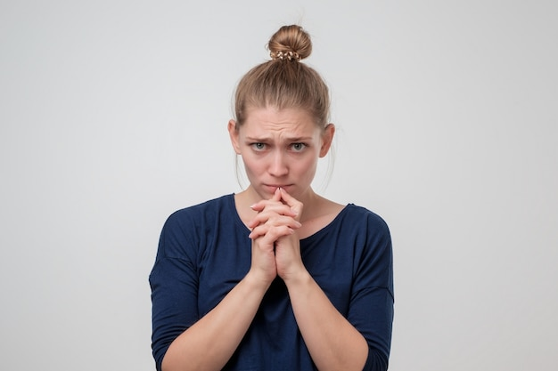 Young caucasian woman with knot is sad because of something.