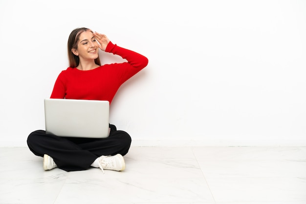 Young caucasian woman with a laptop sitting on the floor has realized something and intending the solution