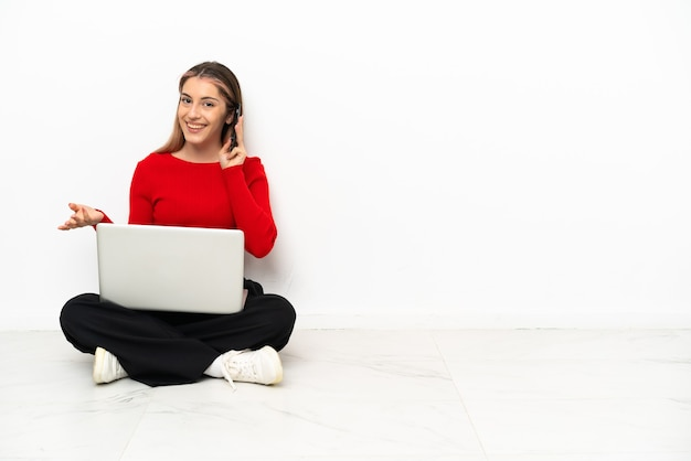 Young caucasian woman with a laptop sitting on the floor keeping a conversation with the mobile phone with someone