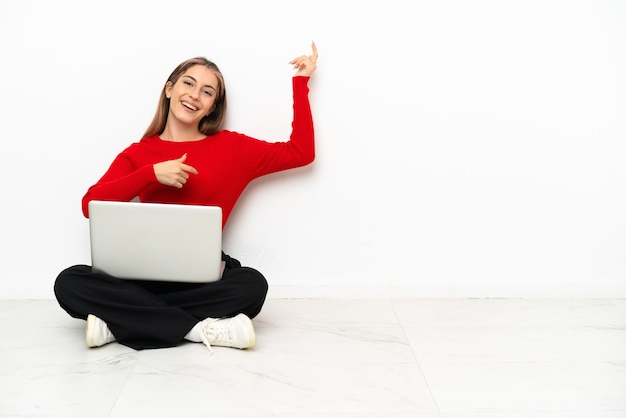 Young caucasian woman with a laptop sitting on the floor making guitar gesture