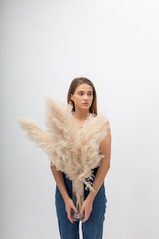 Young caucasian woman with long hair posing at studio, holding pampas grass