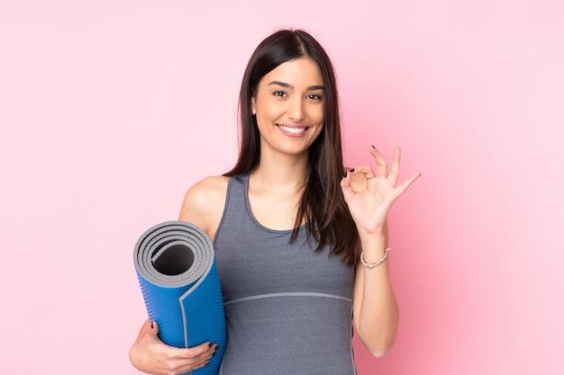 指でokサインを示すピンクの壁に分離されたマットを持つ若い白人女性
