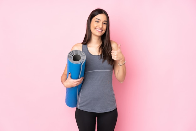 Young caucasian woman with mat isolated on pink wall giving a thumbs up gesture