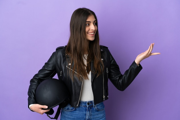 Young caucasian woman with a motorcycle helmet isolated on purple background extending hands to the side for inviting to come