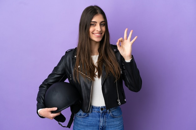 Young caucasian woman with a motorcycle helmet isolated on purple background showing ok sign with fingers