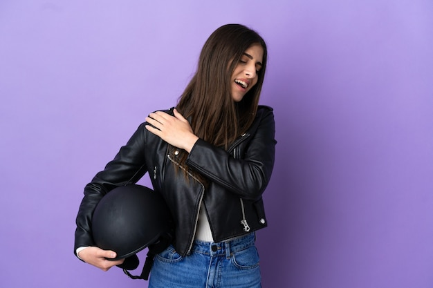 Young caucasian woman with a motorcycle helmet isolated on purple background suffering from pain in shoulder for having made an effort