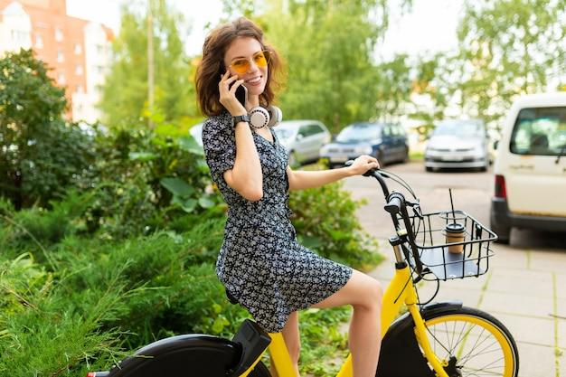 完璧な笑顔、ふくよかな唇、メガネ、イヤホンを持つ若い白人女性、自然の中を歩く、自転車に乗る、電話をかける