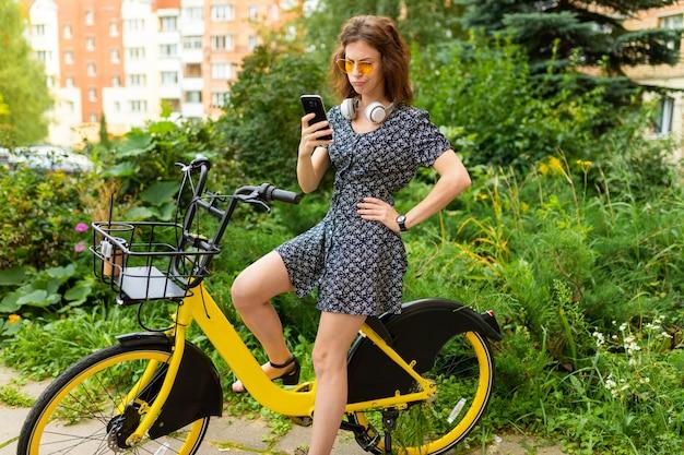 完璧な笑顔、ふくよかな唇、メガネ、イヤホンを持つ若い白人女性、自然の中を歩く、自転車に乗る、電話と疑念を抱く