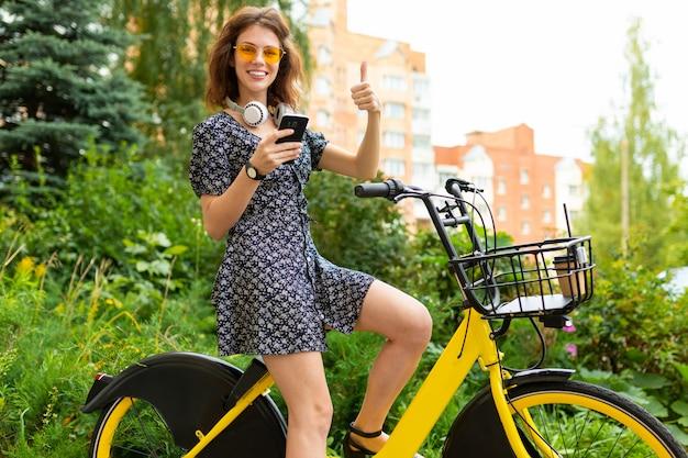 完璧な笑顔、ふくよかな唇、メガネ、イヤホン、自然の中を歩く、自転車に乗る、phneを保持する若い白人女性