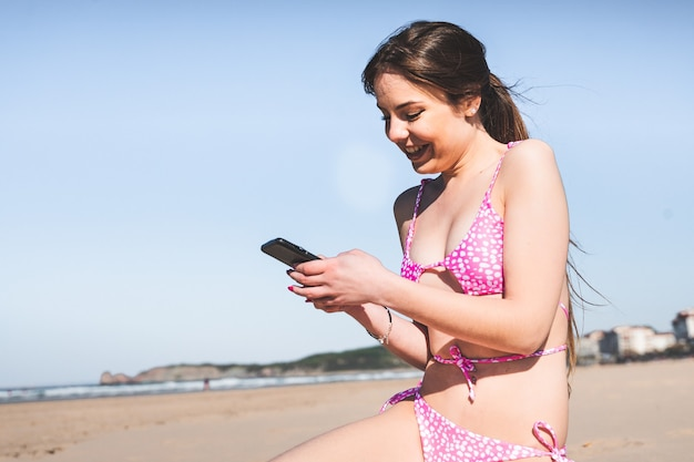 Young caucasian woman with a pink bikini on the beach using a mobile phone
