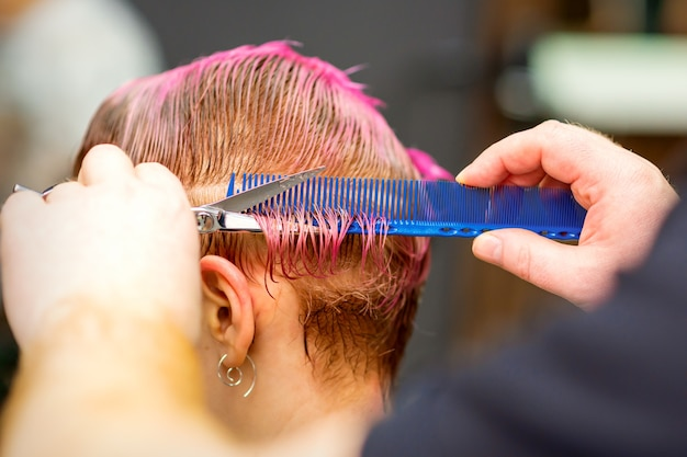 Молодая кавказская женщина с розовыми волосами делает короткую стрижку руками мужского парикмахера в парикмахерской