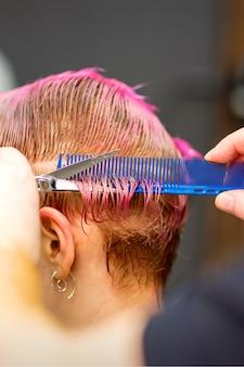Молодая кавказская женщина с розовыми волосами делает короткую стрижку руками мужских парикмахеров в парикмахерской