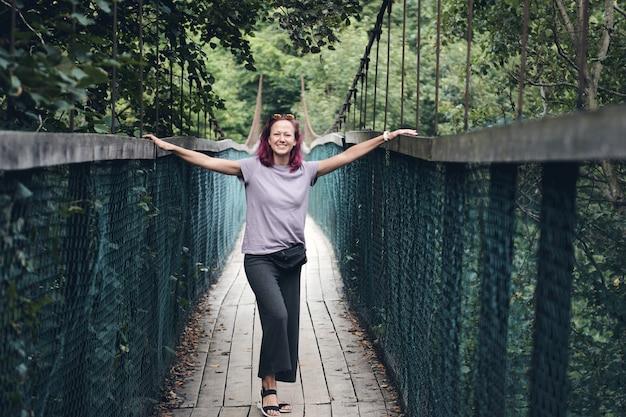 Молодая кавказская женщина с розовыми волосами на длинном стальном подвесном мосту. старый небольшой деревянный мост через реку только для пешеходов. горная река в окружении гор и альпийского леса.