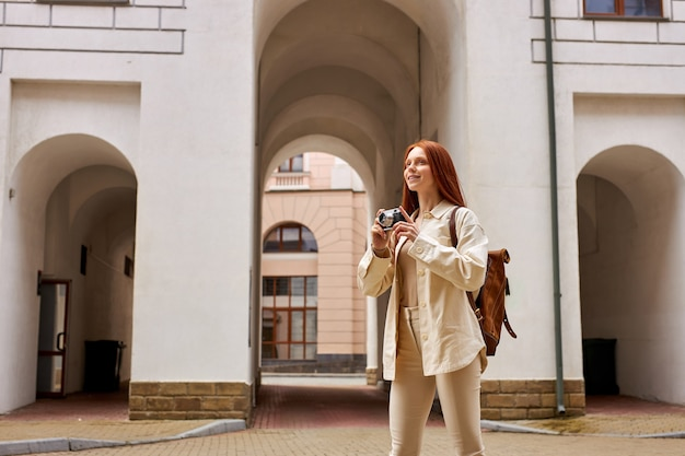 Молодая кавказская женщина с ретро камерой в руках, глядя на старую городскую архитектуру, фотографируя д ...