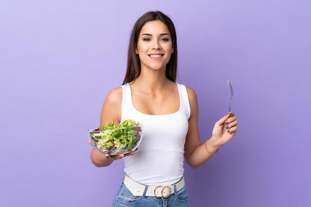 Молодая кавказская женщина с салатом, изолированные на фиолетовом фоне