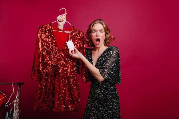 Молодая кавказская женщина с шокированным выражением лица смотрит на цену на блестящее платье