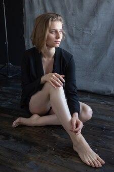 패브릭 배경 앞의 바닥에 앉아 검은 정장 재킷에 짧은 머리를 가진 젊은 백인 여자