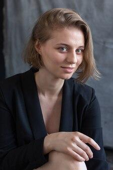 회색 패브릭 배경 앞에 앉아 검은 정장 재킷에 포즈를 취하는 짧은 머리를 가진 젊은 백인 여자
