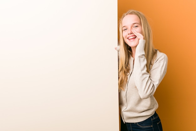 Young caucasian woman with  shouting excited to front.