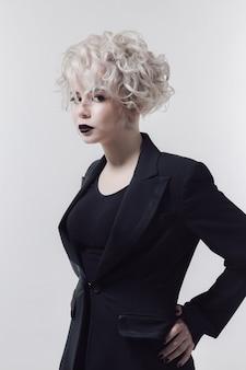 孤立したスタジオでポーズをとってスタイリッシュな髪型の若い白人女性